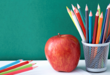 An apple, and assorted school supplies